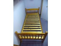 Single pine bed with decorative curtains or bunk bed