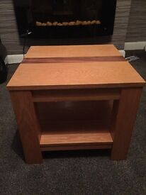 Square coffee table, oak hard wood in a tan colour with a darker strip in the middle.
