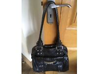 Guess Black Leather handbag with chrome detail. Zip fastening and two handles.