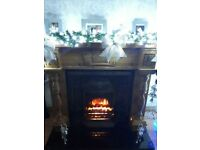 Carved oak fireplace surround and marble hearth with electric fire