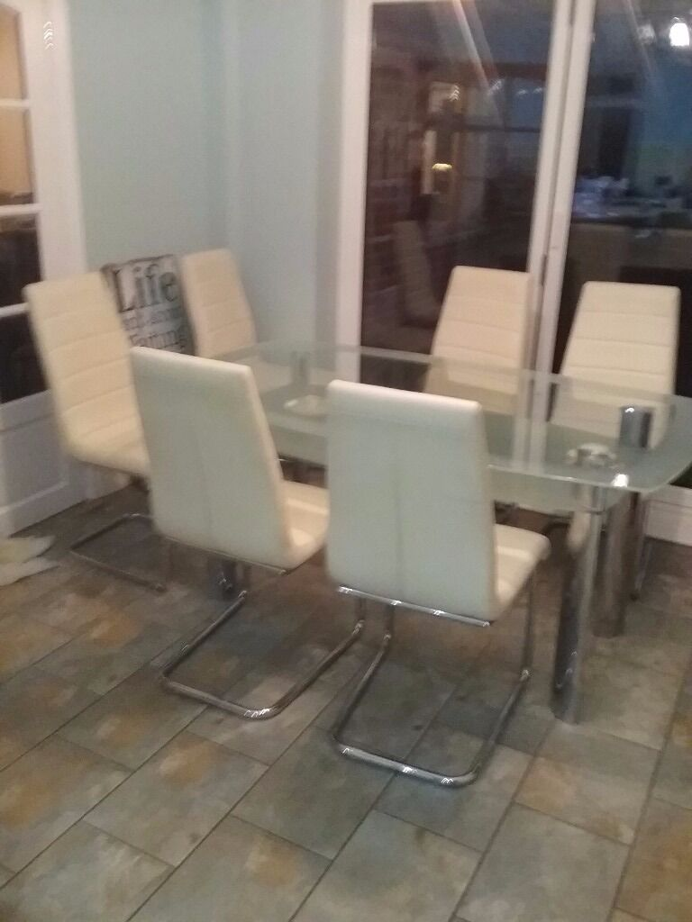 dining table with shelf underneath. glass dining room table with a shelf underneath and 6 cream chairs