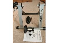PEDAL PRO RACING BIKE HOME TRAINER WITH SPINDLE AND NEW FRONT WHEEL REST.