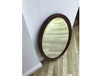 Oval vintage mirror with bevelled edge and dark wood frame. (may be oak, but not sure)