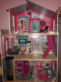 Dolls house with lots of Barbie dolls and accessories