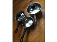 SET OF THREE PANS W/ BLACK HANDLES - TWO LIDS INCLUDED