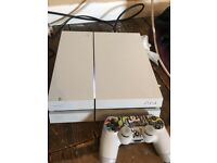 White PlayStation 4 with controller and games
