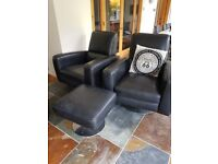 pair of black leather chairs and foot stool