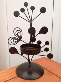 Candle holder ornament, dark brown metal frame with a platform for a tealight or candle in a glass