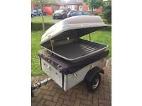 Small camping trailer with roof box