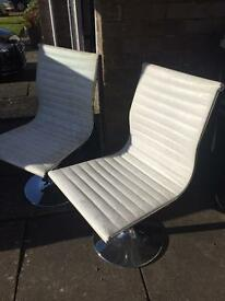 2 white swivel chairs