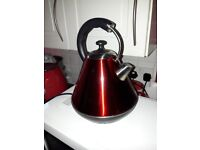 Red kettle with black stand and handle