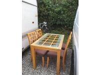 Lovely wooden table with glass lid and 4 chairs in good condition