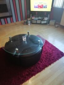 Table coffee table with glass top and black leather base also has four leather stools