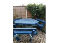 Wooden garden table with seating.