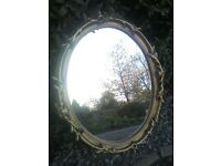 A gold framed oval mirror