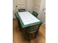 Kitchen table and 4 chairs. White tiled top and green wood.