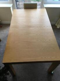 Oak dining table with six faux leather chairs