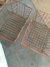 Two copper coloured wire baskets with handles