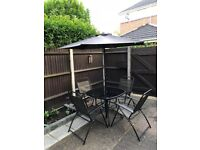 Like-new Garden Set with Glass-top Table, 4 Chairs with Armrests and Parasol