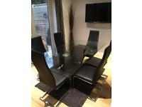 Solid glass dining room table with 8 solid leather chairs