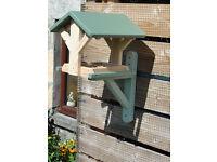 Handcrafted wooden bird feeder sitting on a bracket