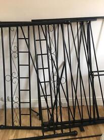 Black metal double bed frame with Sealy mattress.