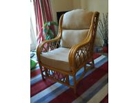 Large wicker chair with cream cushions