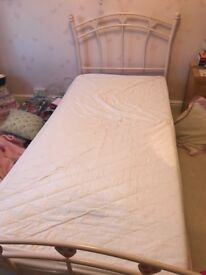 Pink metal frame child's bed with mattress