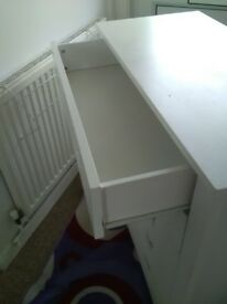 White chest of drawers and bedside table
