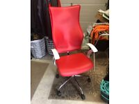 Red designer office swivel chair with arms and wheels