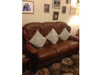 Three piece Italian leather chesterfield suite, with dark wood trim