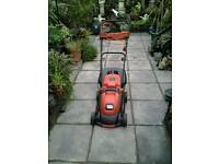 Black & Decker electric lawnmower with grass collection box and three garden rakes.