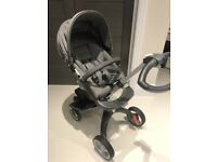 Stokke black melange pushchair, comes with carrycot and changing bag.