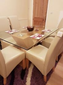Glass top dining table with 6 leather cream high back chairs