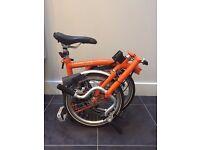 Barely used folding Brompton bike in orange