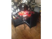 Stunning glass dining table with 4 black leather chairs