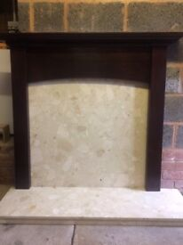 Dark wood mantelpiece surrounding a marble hearth with back panel