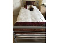Single beds finished in silver grey tubular metal
