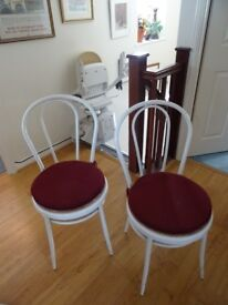 Two white metal bistro chairs with cane seat and removable pads. pick up oly