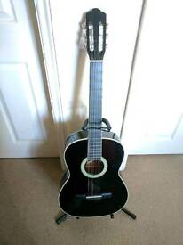 Black accouatic guitar with stand