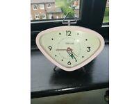 Small pink retro style alarm clock