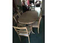 Light wood extending dining table and six chairs, two of which are carving chairs