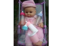 Giggling baby with bib bottles cup hat and pushchair