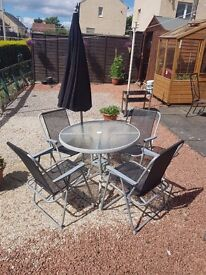 Sliver glass table and chairs plus parasole