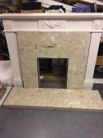 A Wooden fireplace with marble backplate and matching hearth stone.