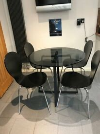 Tempered glass cicular dining table and 4 chairs. 90 cm diameter. Chairs stackable.