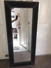 Large mirror, brown material edging with white stitch piping.