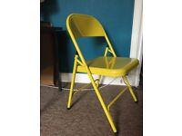 Yellow metal folding chair