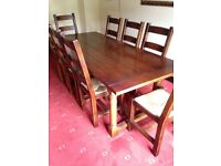 Solid Oak refectory dining table and 8 ladder back chairs.