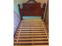 Wooden king size bed, mahogany red. Beautiful metalwork on headboard.